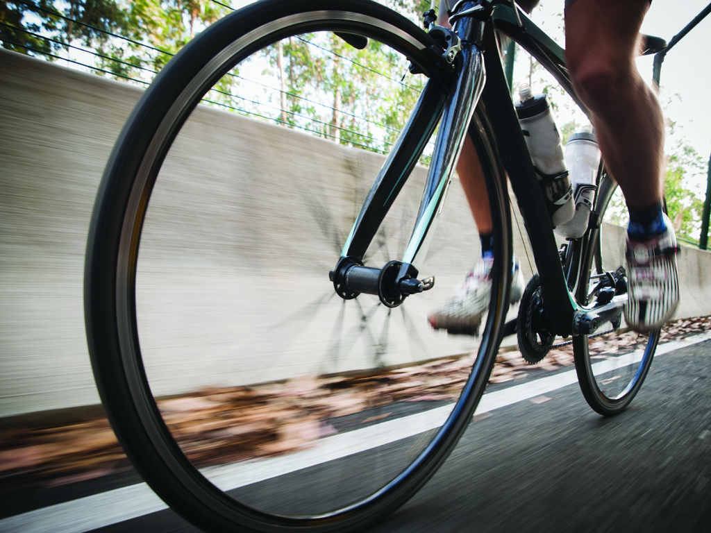 Detail of a road bike with a cyclist pedaling on a road. Photo is taken in low angle composition.